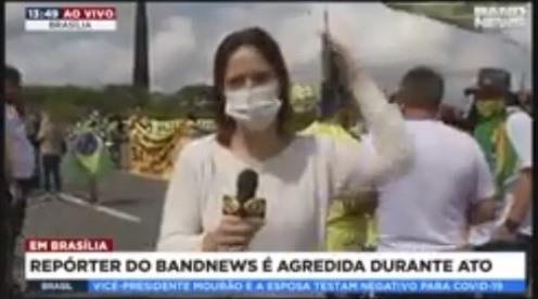 Apoiadora de Bolsonaro dá bandeirada na cabeça de repórter em ato.